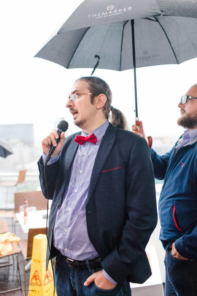 Silviu and Max, being rained on, while presenting the event